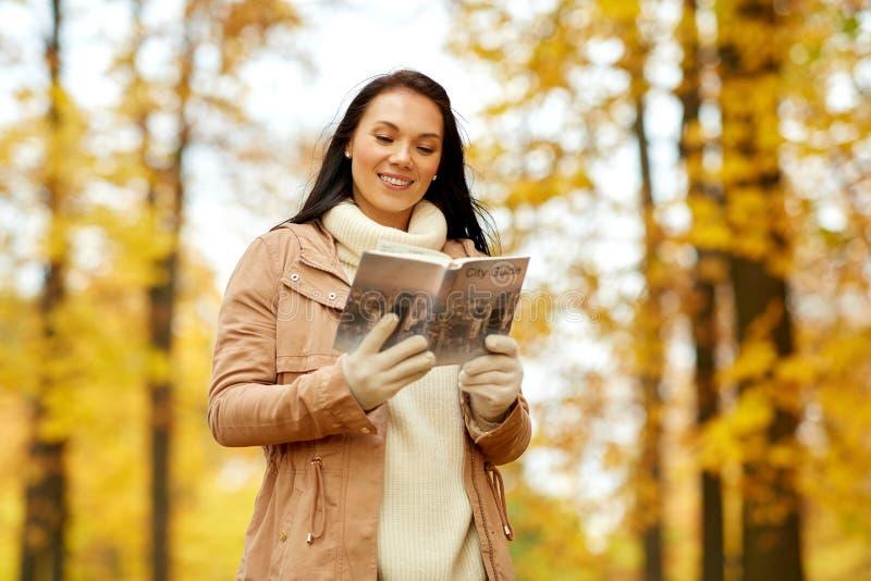 Jeune femme heureuse avec le guide de ville en parc d'automne image stock