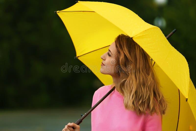 Jeune femme heureuse avec le parapluie lumineux sous la pluie images libres de droits
