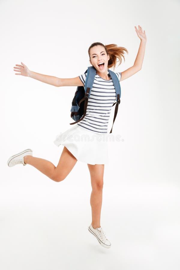 Jeune femme heureuse avec le sac à dos sautant et célébrant le succès images stock