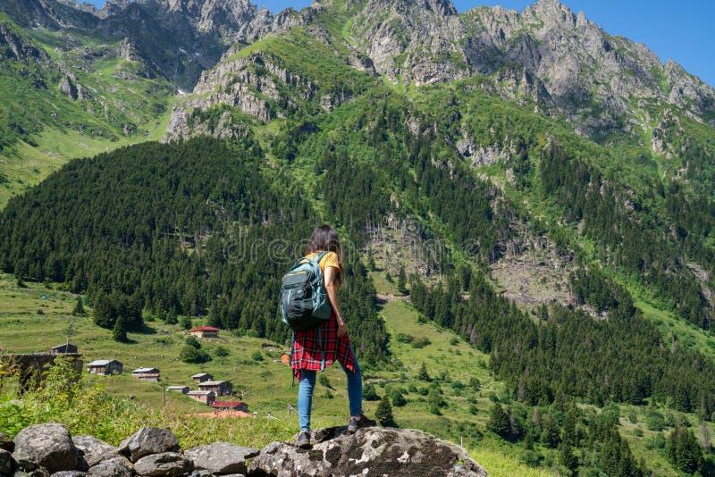 Jeune femme heureuse avec le sac à dos se tenant sur une roche avec les mains augmentées et regardant à une vallée ci-dessous photo stock