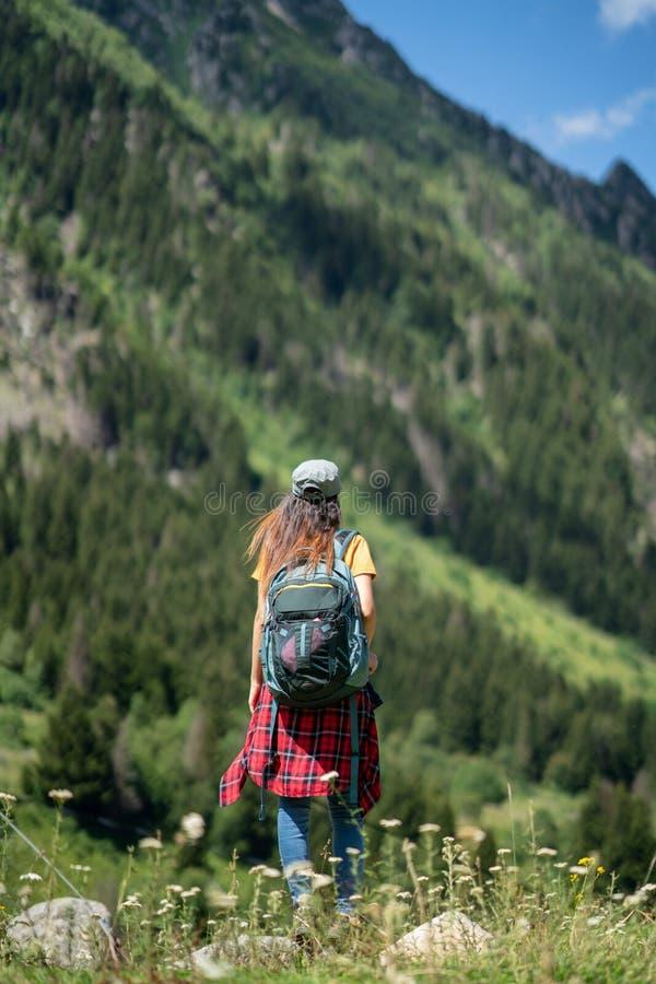 Jeune femme heureuse avec le sac à dos se tenant sur une roche avec les mains augmentées et regardant à une vallée ci-dessous photographie stock