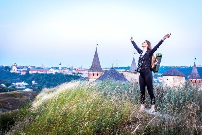 Jeune femme heureuse avec le sac à dos se tenant sur une roche avec les mains augmentées et regardant à une vallée ci-dessous images stock
