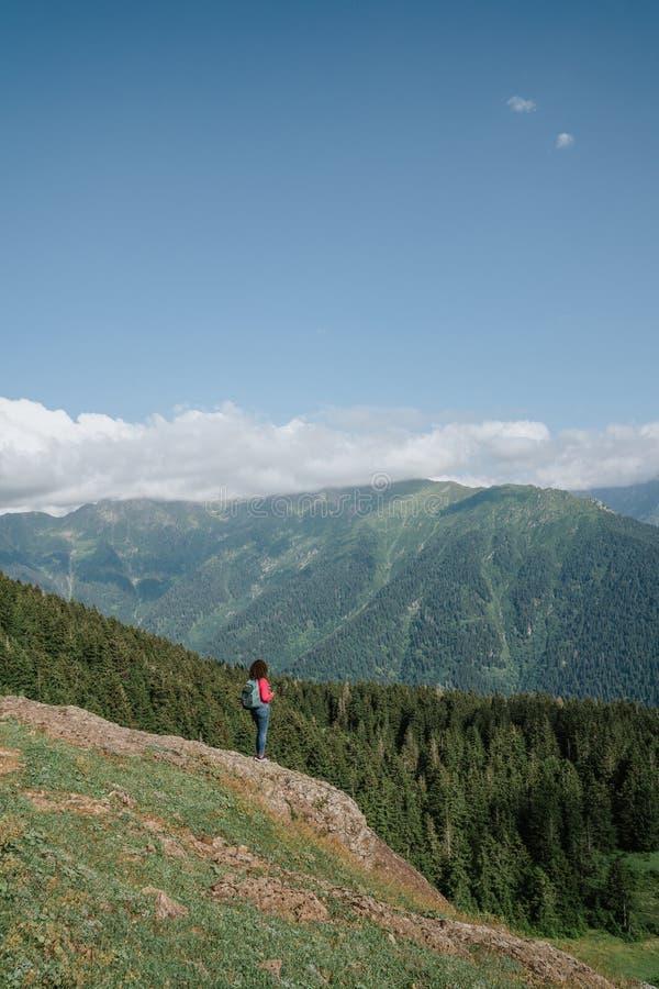 Jeune femme heureuse avec le sac à dos se tenant sur une roche regardant à une vallée ci-dessous images stock