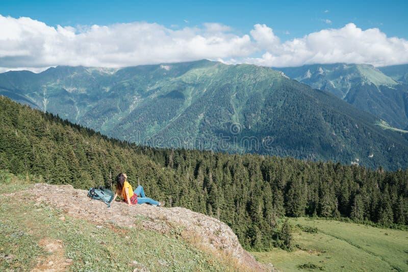 Jeune femme heureuse avec le sac à dos se tenant sur une roche regardant à une vallée ci-dessous image stock