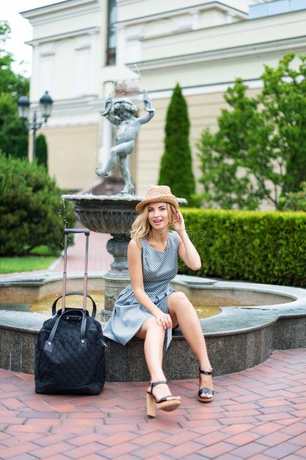 jeune femme heureuse avec le sac de voyage en parc images stock