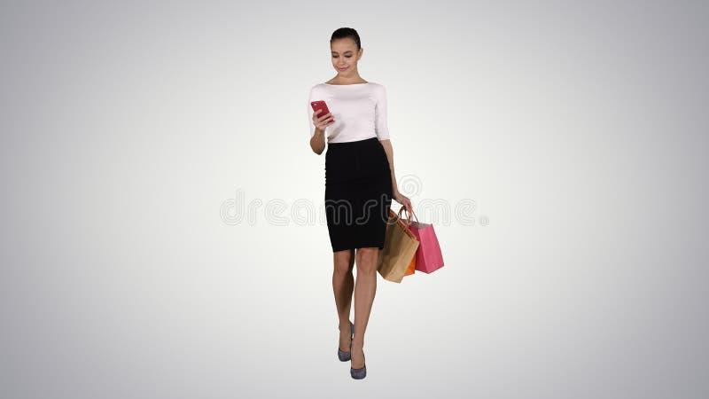 Jeune femme heureuse avec le smartphone faisant l'image de ses sacs à provisions sur le fond de gradient photos libres de droits