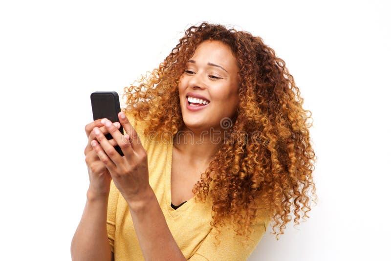 Jeune femme heureuse avec le téléphone portable de participation de cheveux bouclés par le fond blanc photo stock