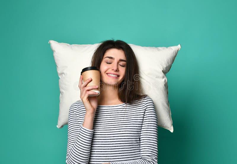 Jeune femme heureuse avec une tasse de café ou de thé dans des ses mains, rêves sur un oreiller au sujet de n'importe quoi photo libre de droits