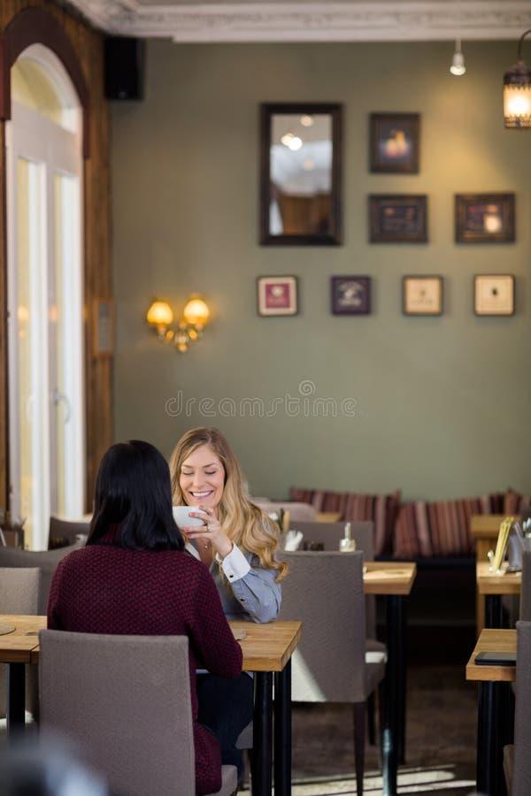 Jeune femme heureuse ayant le café avec l'ami image stock