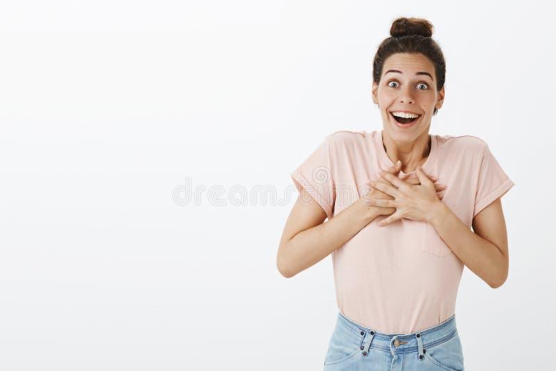 Jeune femme heureuse belle reconnaissante et reconnaissante avec le petit pain malpropre dans le T-shirt et des jeans tenant des  photo stock