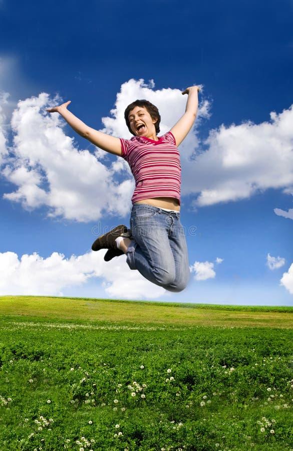 Jeune femme heureuse branchant haut contre le ciel bleu photographie stock libre de droits
