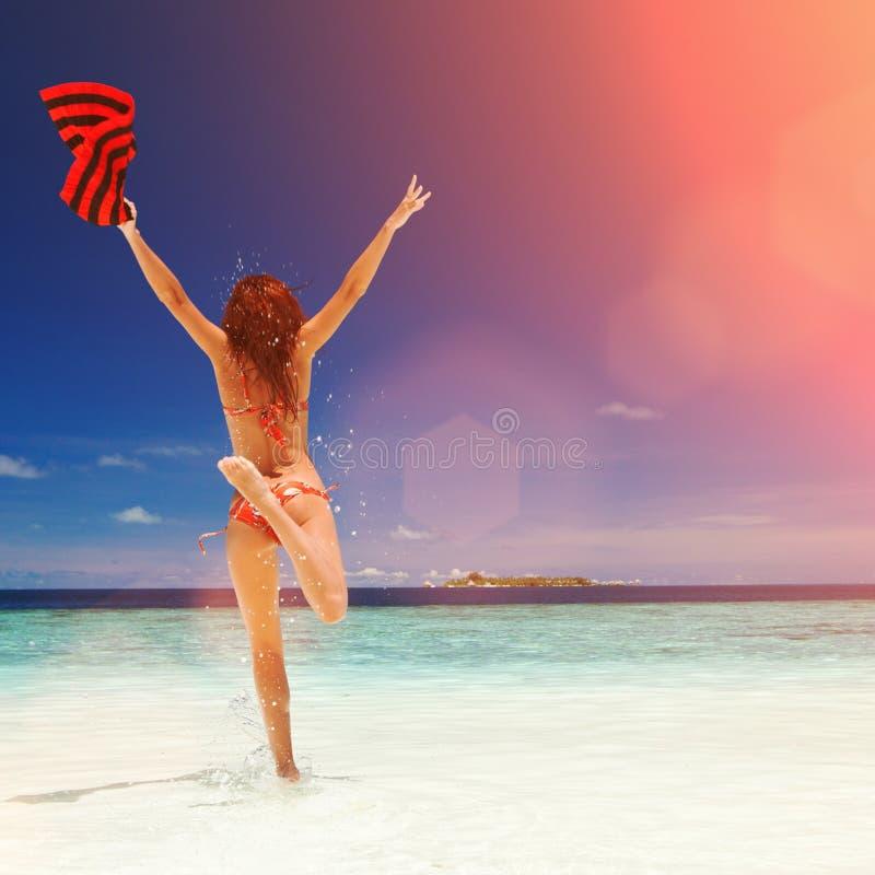 Jeune femme heureuse branchant sur la plage Style de vie heureux photos stock