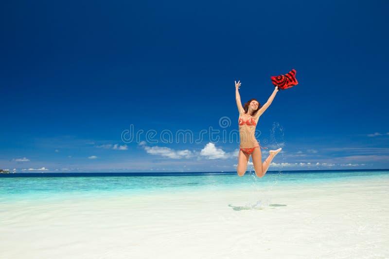 Jeune femme heureuse branchant sur la plage Style de vie heureux Sable blanc, ciel bleu et mer de cristal de plage tropicale images libres de droits