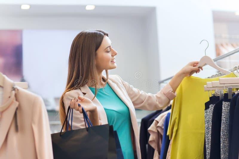 Jeune femme heureuse choisissant des vêtements dans le mail photos stock