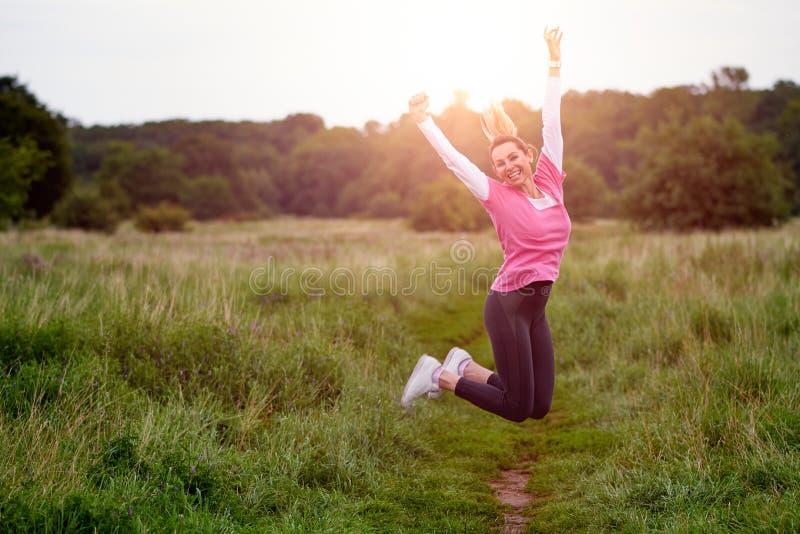 Jeune femme heureuse convenable dans le sportwear sautant dans l'air photographie stock