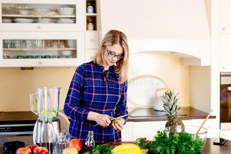 Jeune femme heureuse coupant en tranches des fruits pour le smoothie photos stock