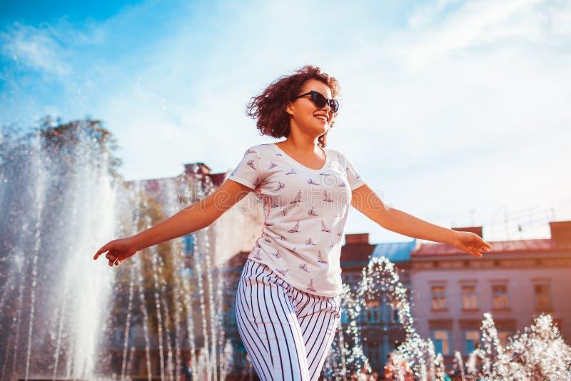 Jeune femme heureuse courant sur le fond de fontaine sur la rue d'été images stock