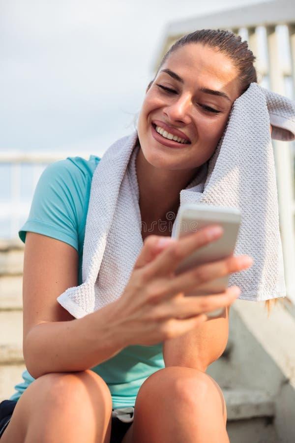 Jeune femme heureuse détendant après la séance d'entraînement photos stock