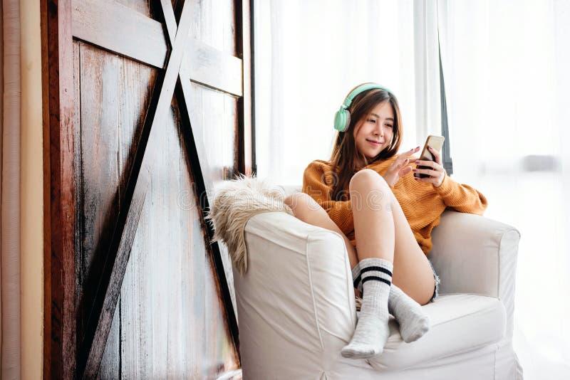 Jeune femme heureuse détendant par l'écouteur de musique de Smartphone sur le sofa dans la Chambre confortable photos libres de droits