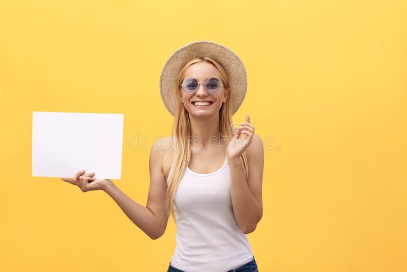 Jeune femme heureuse d'étudiant montrant le bloc-notes vide, sur le fond jaune images libres de droits