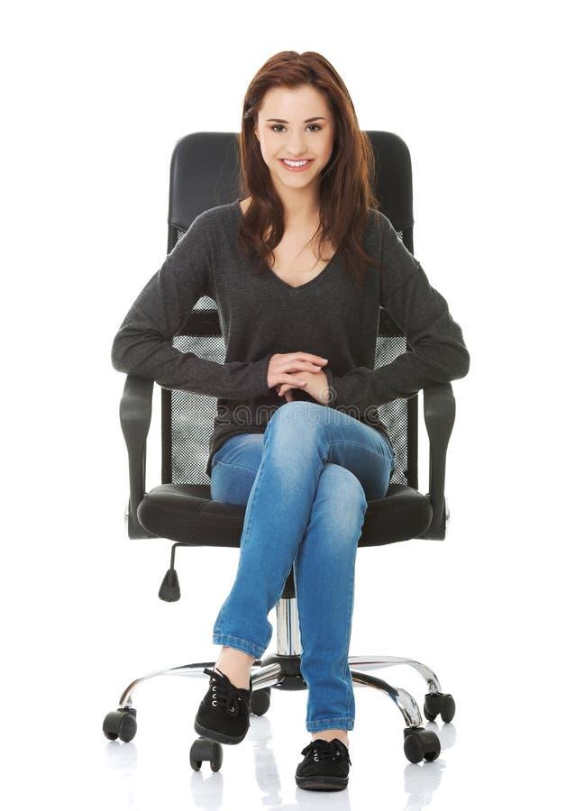 Jeune femme heureuse d'étudiant s'asseyant sur un fauteuil roulant images libres de droits