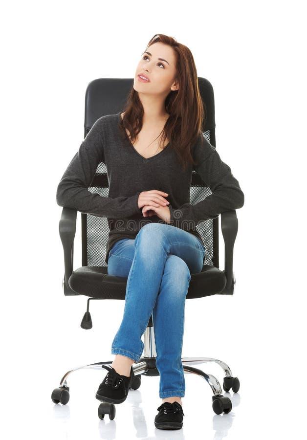 Jeune femme heureuse d'étudiant s'asseyant sur un fauteuil roulant photographie stock libre de droits