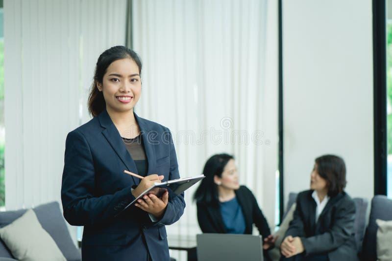 Jeune femme heureuse d'affaires avec son personnel, groupe de personnes à l'arrière-plan au bureau lumineux moderne à l'intérieur images stock