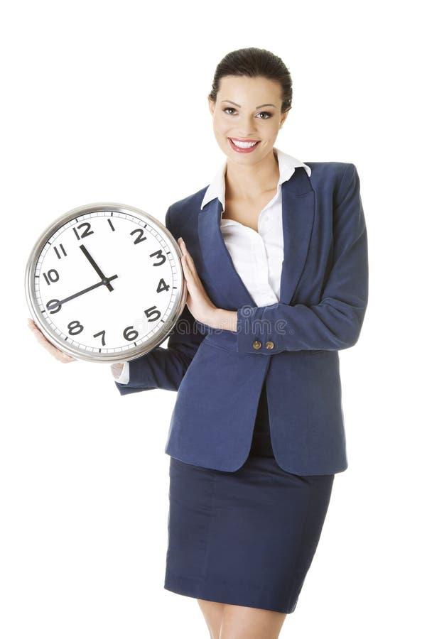 Jeune femme heureuse d'affaires retenant l'horloge de bureau images stock