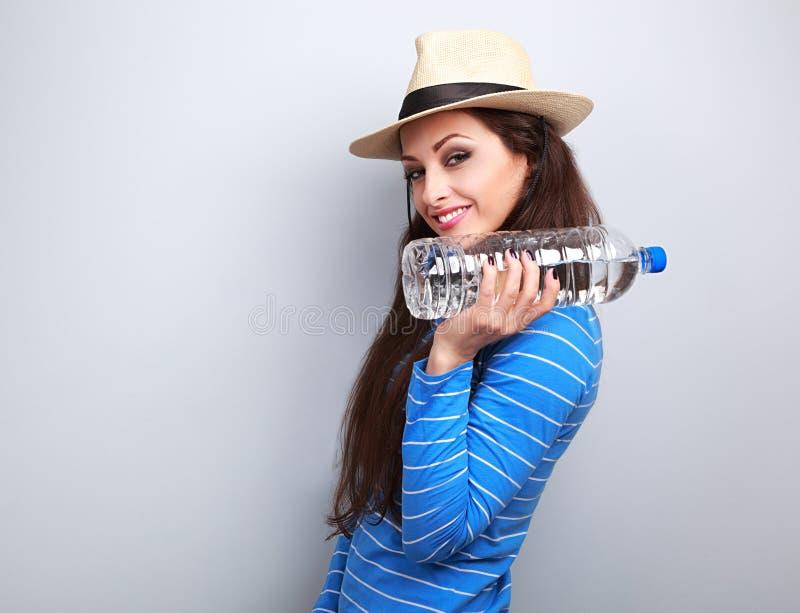 Jeune femme heureuse d'amusement tenant la bouteille de l'eau pure avec naturel photos stock