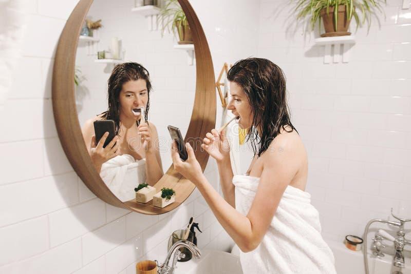 Jeune femme heureuse dans des dents de brossage de serviette blanche et regarder le smartphone dans la salle de bains avec le mir photographie stock libre de droits