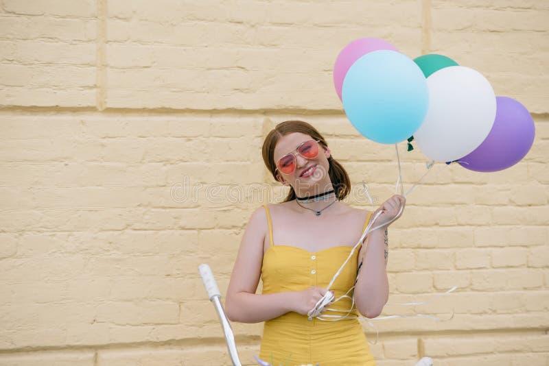 jeune femme heureuse dans des lunettes de soleil souriant à la caméra et tenant des ballons tout en se tenant avec la bicyclette image stock