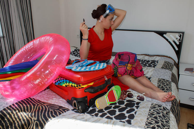 Jeune femme heureuse dans l'équipement coloré d'été près de la valise fournie de personnel rouge photo libre de droits