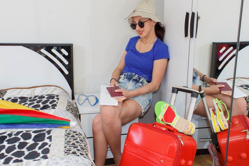 Jeune femme heureuse dans l'équipement coloré d'été se reposant près de la valise fournie de personnel rouge photo libre de droits
