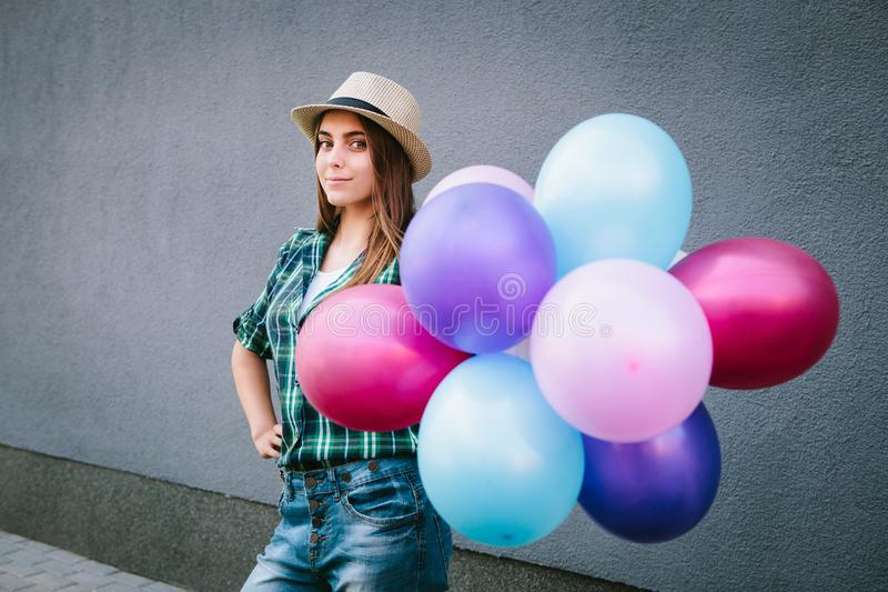 Jeune femme heureuse dans la chemise et le chapeau de plaid se tenant avec des ballons et le sourire photographie stock libre de droits