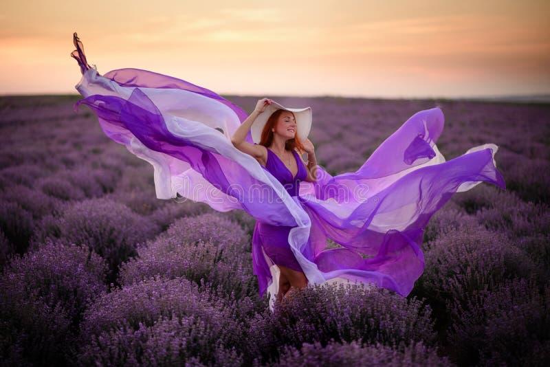 Jeune femme heureuse dans la position pourpre luxueuse de robe dans le domaine de lavande image stock