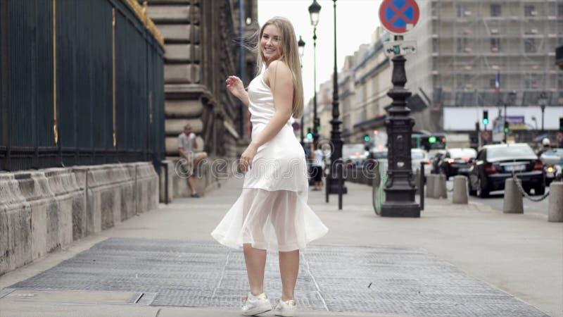 Jeune femme heureuse dans la robe blanche posant sur des rues de ville de fond action Blonde attirante souriant et posant dedans image libre de droits
