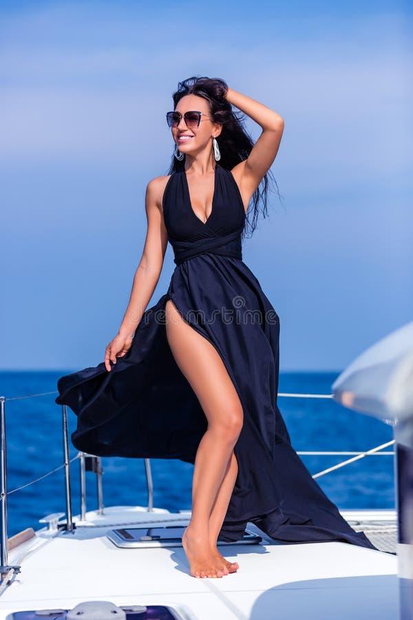 Jeune femme heureuse dans la robe noire appréciant égalisant le soleil au yacht photos libres de droits