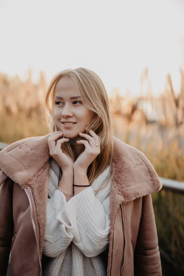 Jeune femme heureuse dans la saison d'automne sur une rue de ville sur le lever de soleil photographie stock libre de droits