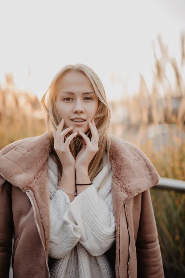 Jeune femme heureuse dans la saison d'automne sur une rue de ville sur le lever de soleil photo stock