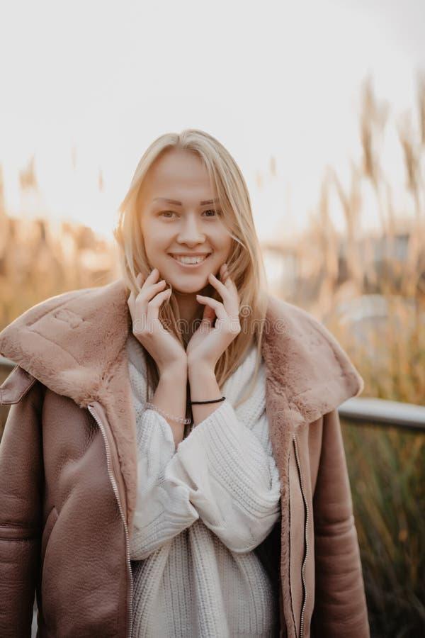 Jeune femme heureuse dans la saison d'automne sur une rue de ville sur le lever de soleil photos stock