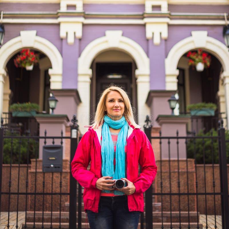 Jeune femme heureuse dans la veste rouge avec l'appareil-photo dessus image libre de droits
