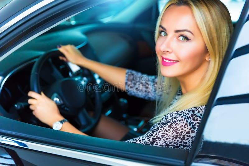 Jeune femme heureuse dans la voiture de luxe moderne images stock