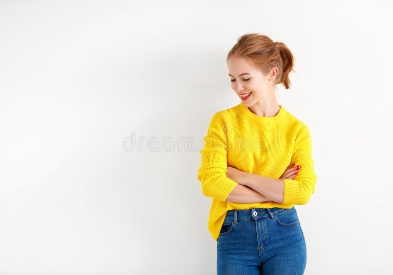 Jeune femme heureuse dans le chandail jaune sur le fond blanc images stock