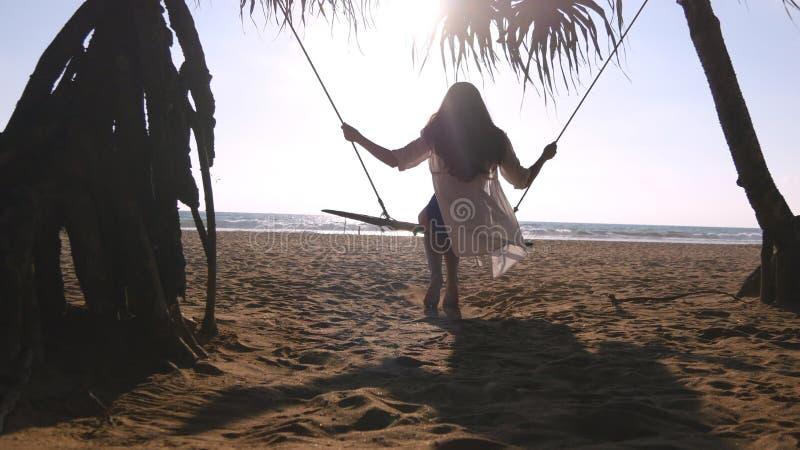 Jeune femme heureuse dans le maillot de bain et la chemise détendant à l'oscillation à la plage tropicale d'océan Belle fille s'a photo libre de droits