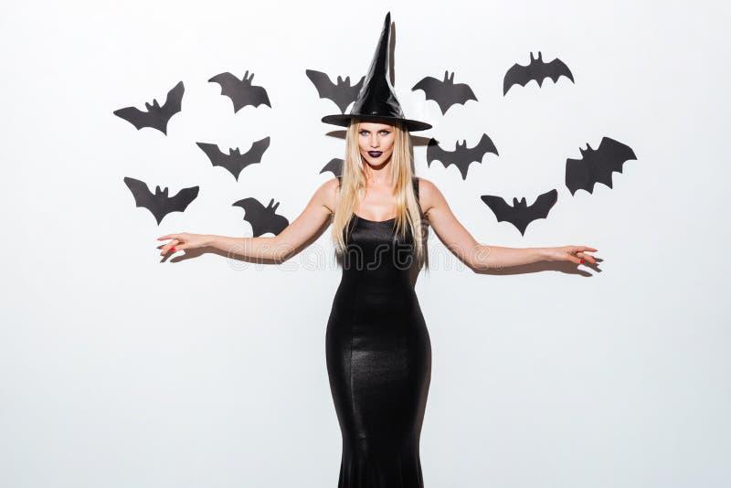 Jeune femme heureuse dans le noir qui costume de Halloween avec le chapeau image libre de droits