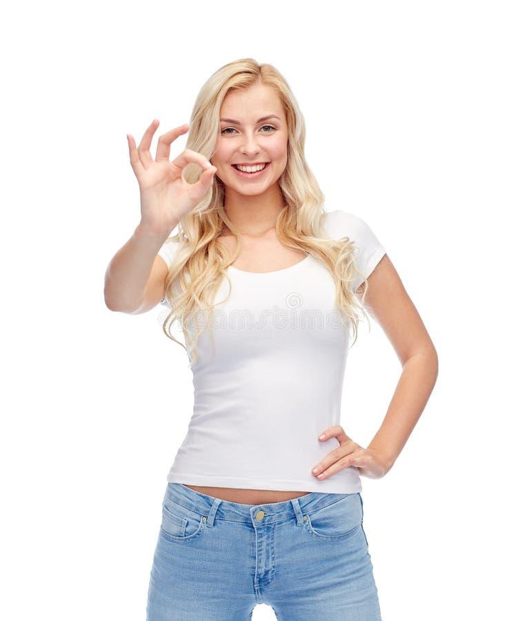 Jeune femme heureuse dans le T-shirt blanc montrant le signe correct photo stock