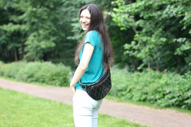 Jeune femme heureuse dans le T-shirt en bon état et des jeans blancs avec le le moderne photos stock