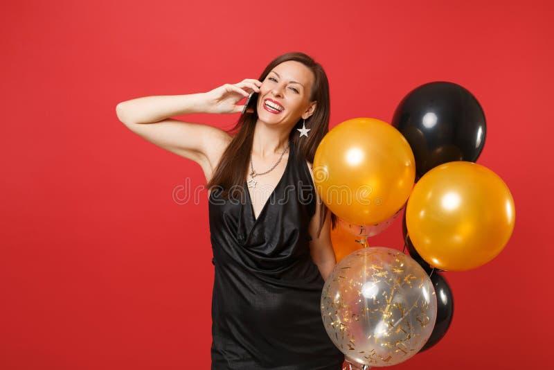 Jeune femme heureuse dans peu de robe noire tenant des ballons à air parlant au téléphone portable, conversation agréable de cond images stock