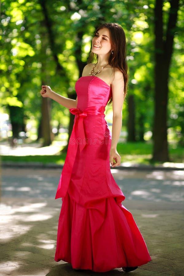 Jeune femme heureuse dans une longue robe de luxe en parc d'été photos stock