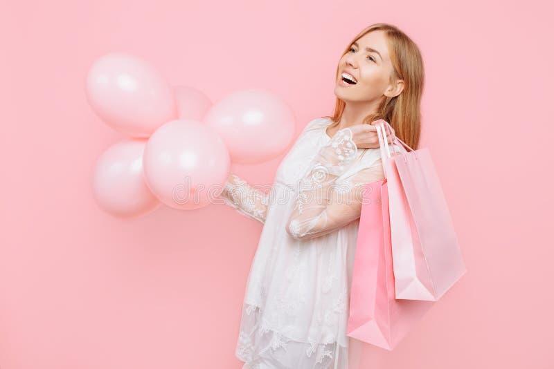 Jeune femme heureuse, dans une robe blanche, avec des sacs dans les mains et des ballons, sur un fond rose Concept d'achats images stock